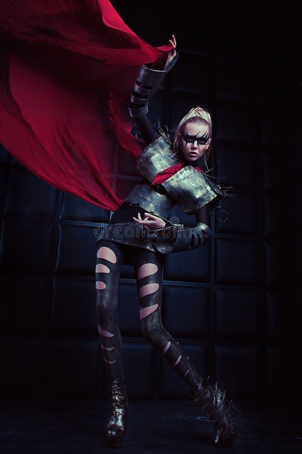Donna bionda nella posa d'acciaio dell'armatura fotografie stock libere da diritti