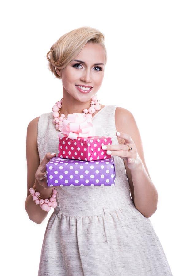 Donna bionda piacevole con bello trucco che tiene i contenitori di regalo porpora e rosa fotografia stock