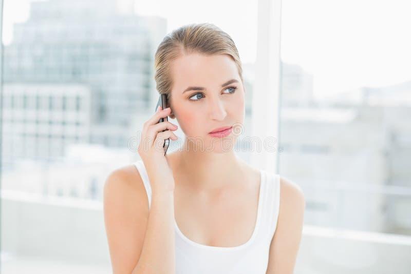 Donna bionda premurosa sul telefono immagini stock