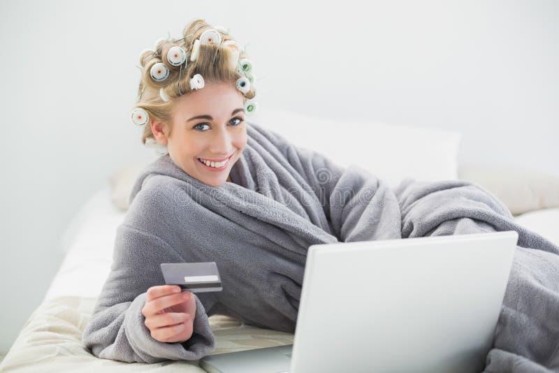 Donna bionda rilassata allegra in bigodini che compra online con il suo computer portatile immagine stock