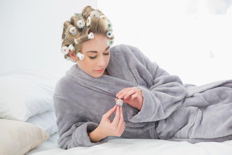 Donna bionda rilassata concentrata in bigodini che aprono un vaso di smalto fotografia stock libera da diritti