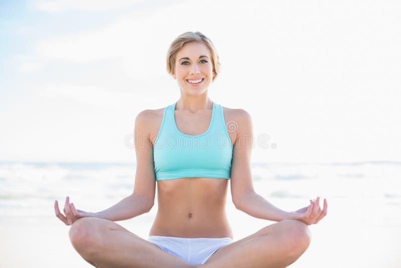 Donna bionda rilassata nell'yoga di pratica degli abiti sportivi fotografia stock