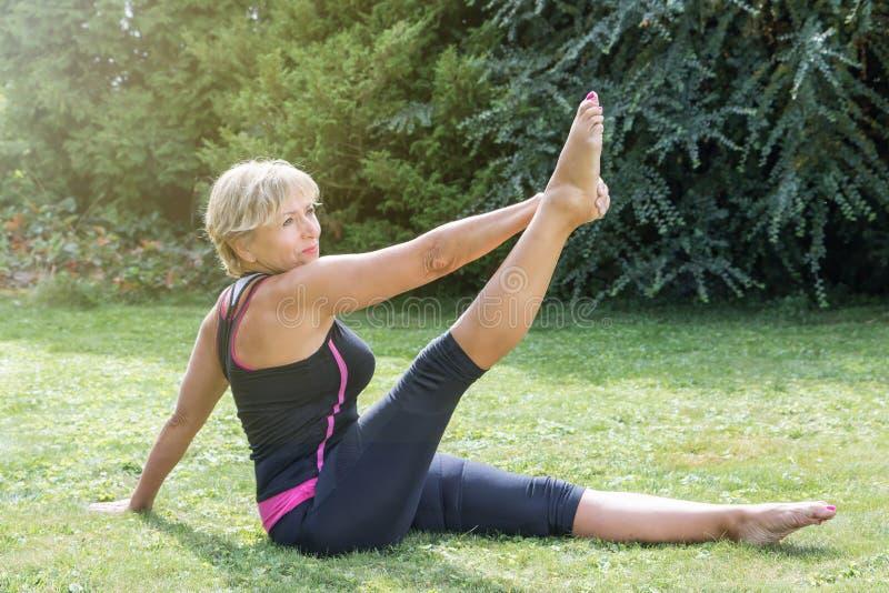 Donna bionda senior attraente nella singola posizione diritta di allungamento della gamba fotografia stock