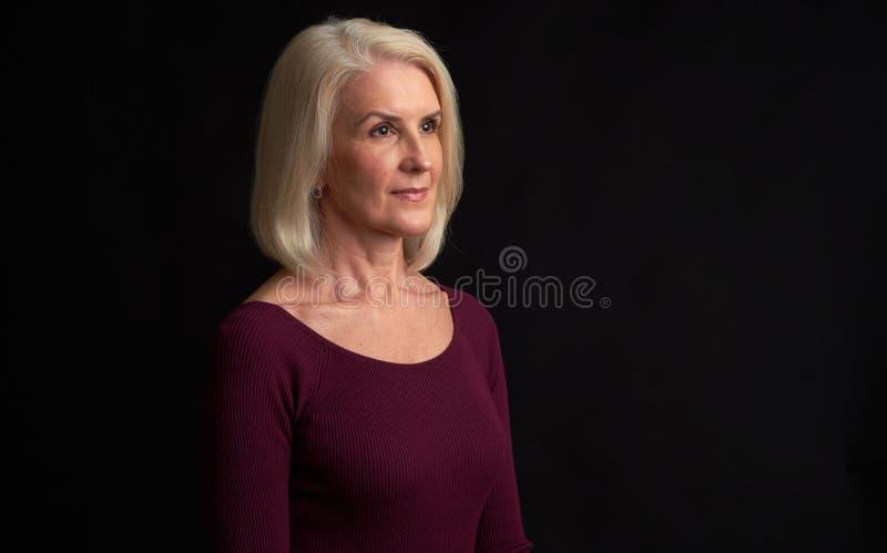 Donna bionda senior che distoglie lo sguardo isolata sul nero immagini stock libere da diritti