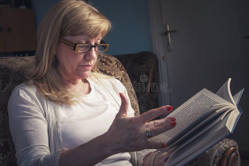 Donna bionda senior che legge un libro fotografia stock libera da diritti