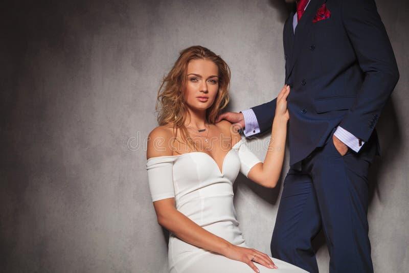 Donna bionda sexy che tiene il suo amante dal suo vestito fotografia stock