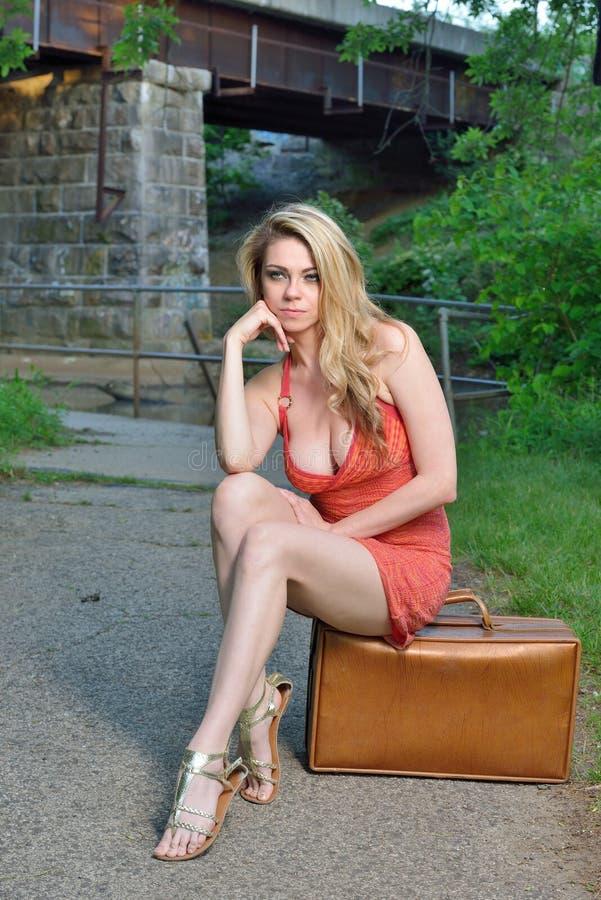 Donna bionda sexy con la valigia immagine stock