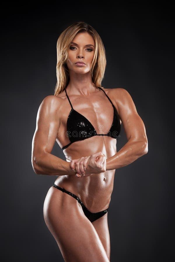 Donna bionda sexy del culturista in bikini nero. fotografie stock libere da diritti
