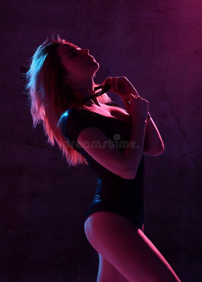 Donna bionda sexy di bello modo che posa alla luce al neon blu e rosa di modo in occhiali da sole e biancheria intima fotografia stock