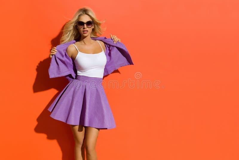 Donna bionda sexy in occhiali da sole, Violet Mini Skirt And Unbuttoned Jacket fotografia stock libera da diritti