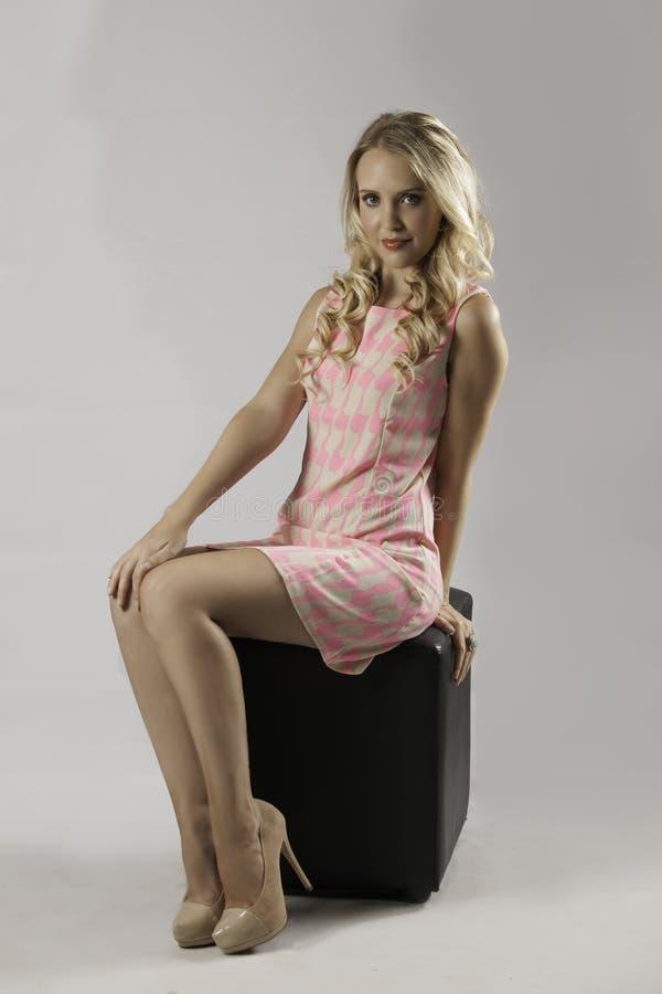 Donna bionda sexy in vestito rosa modellato fotografie stock