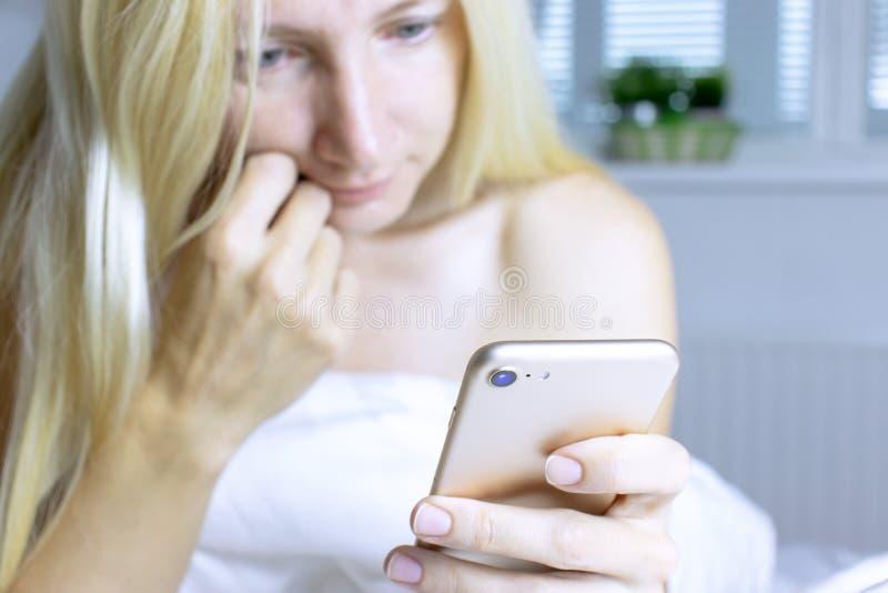 Donna bionda sorridente Blurred che si siede su un letto con lettiera bianca e che per mezzo di uno smartphone immagini stock libere da diritti