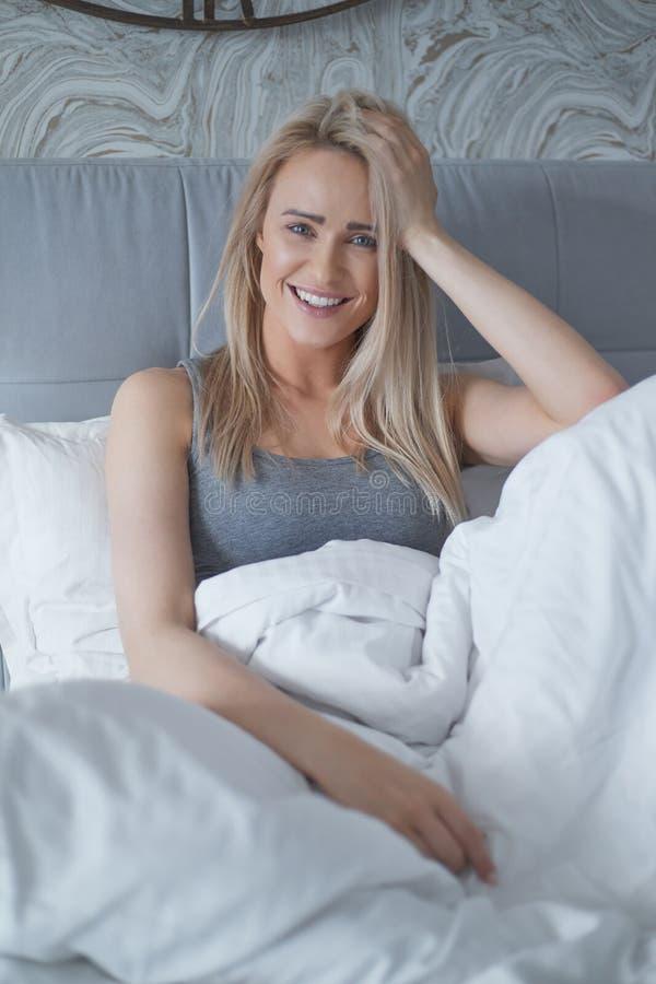Donna bionda sorridente che si siede nel suo letto in camera da letto luminosa sotto la trapunta immagine stock