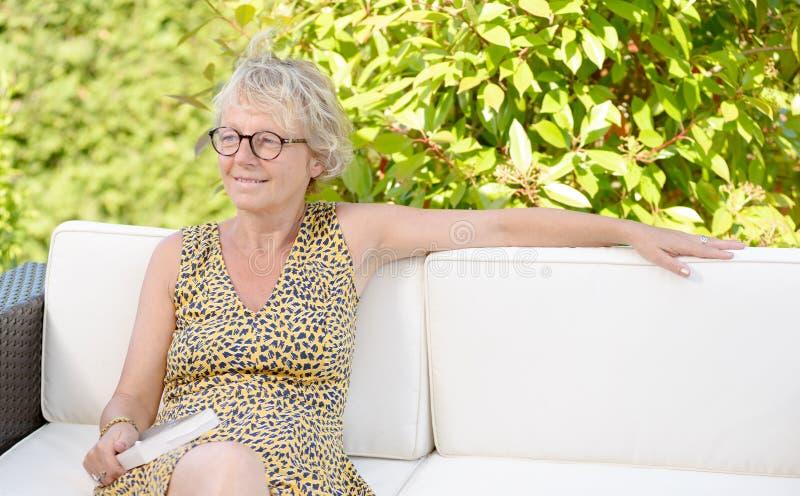 Donna bionda sorridente che si siede sul sofà fotografia stock