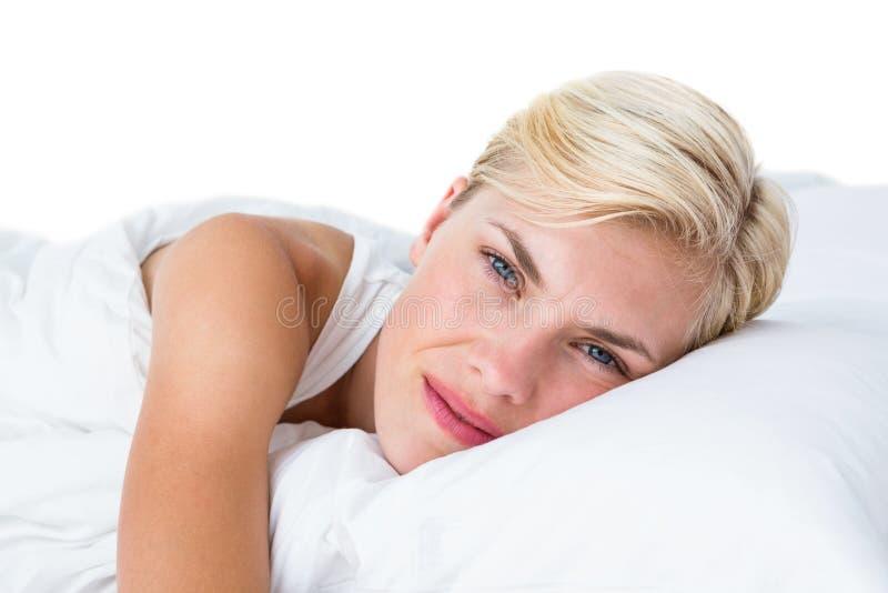 Donna bionda sorridente che si trova nel suo letto fotografia stock libera da diritti