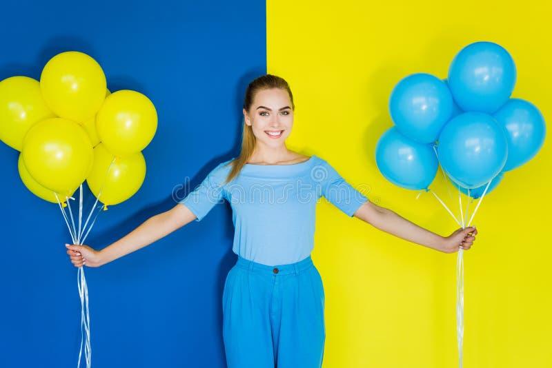 Donna bionda sorridente che tiene i palloni blu e gialli sul blu fotografia stock
