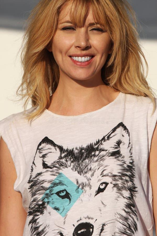Donna bionda sorridente con la maglietta del lupo fotografia stock