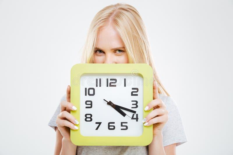 Donna bionda sorridente sveglia che dà una occhiata dall'orologio di parete fotografia stock