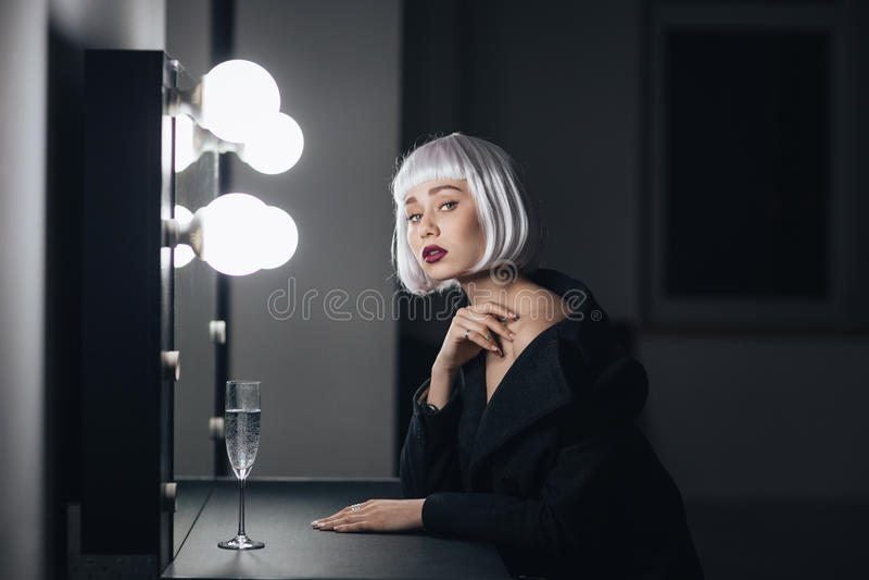 Donna bionda splendida che si siede nello spogliatoio immagine stock
