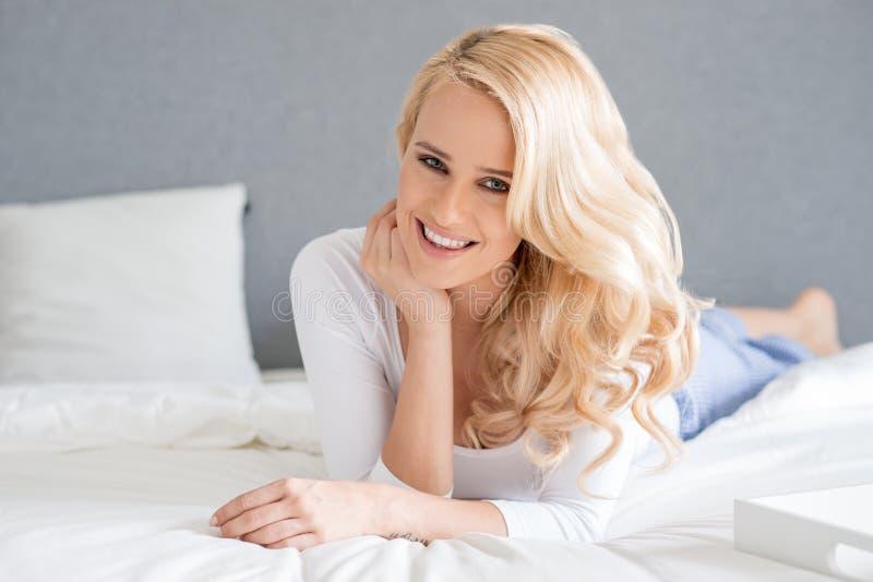 Donna bionda splendida che si trova sul suo letto fotografia stock libera da diritti