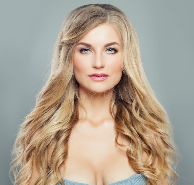 Donna bionda splendida con capelli ricci sani lunghi e chiara pelle Trattamento, haircare e cosmetologia facciali immagini stock