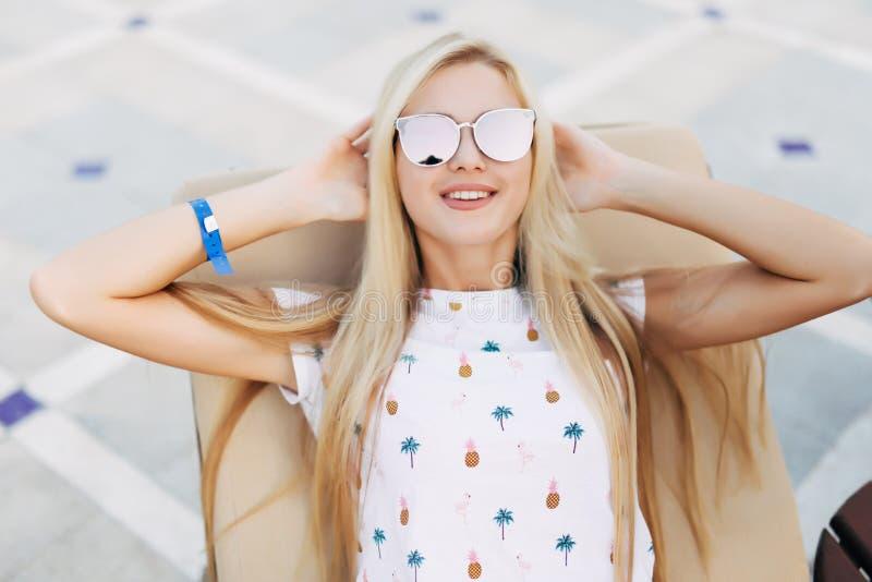 Donna bionda splendida con gli occhiali da sole che bighellonano all'aperto da una piscina un giorno di estate immagini stock