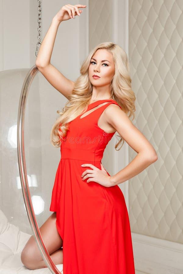 Donna bionda splendida sensuale in vestito rosso luminoso con trucco e la condizione riccia lunga dell'acconciatura che posano e  immagine stock