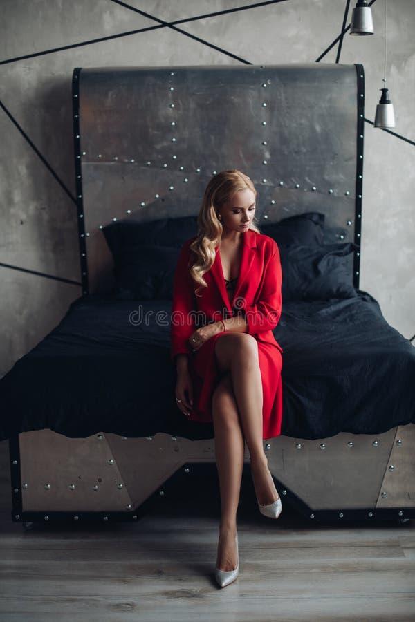 Donna bionda splendida in vestito rosso che esamina macchina fotografica fotografia stock libera da diritti