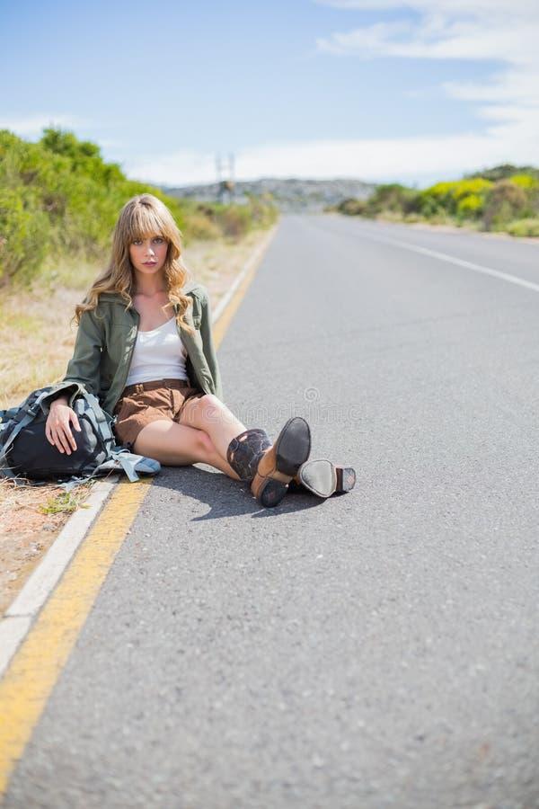 Donna bionda stanca che si siede sul bordo della strada immagini stock libere da diritti