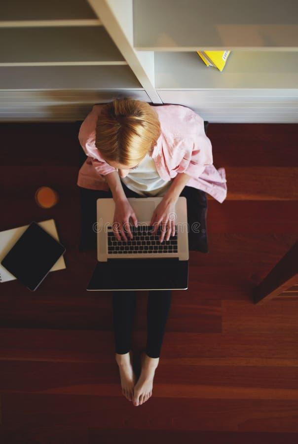 Donna bionda sveglia che si siede a casa sul pavimento con un computer sul suo rivestimento fotografia stock libera da diritti