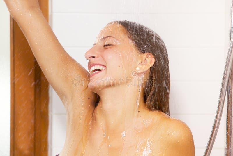 Donna bionda sveglia che sorride nella doccia felice fotografia stock