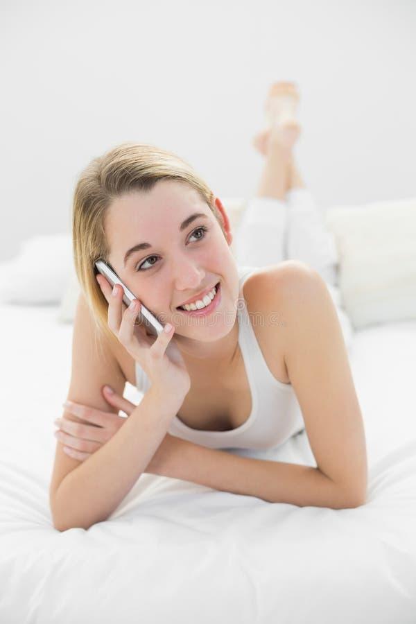 Donna bionda sveglia che telefona con il suo smartphone che si trova sul suo letto a casa fotografia stock