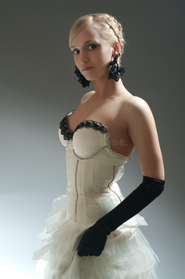 Donna bionda in vestito bianco ed in guanti neri immagini stock