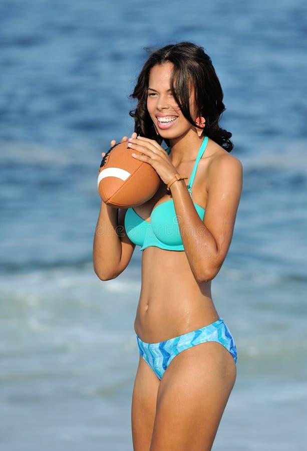 Donna biracial Stunning alla spiaggia con gioco del calcio fotografia stock libera da diritti