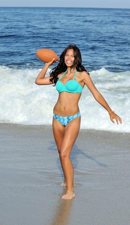Donna biracial Stunning alla spiaggia con gioco del calcio fotografie stock libere da diritti