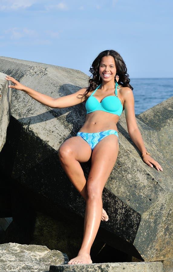 Donna biracial Stunning alla spiaggia contro il molo fotografia stock