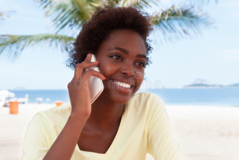 Donna brasiliana alla spiaggia che flirta al telefono fotografie stock