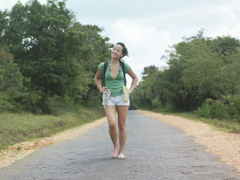 Donna in breve Barefeet di camminata sulla strada rurale immagine stock
