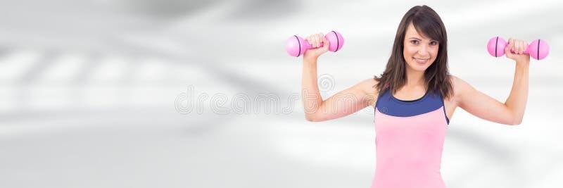 Donna in buona salute esile che tiene i pesi fotografia stock
