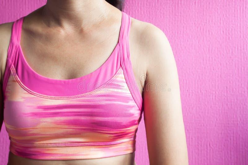 Donna in buona salute nel reggiseno rosa di sport su fondo rosa, cance del seno immagini stock