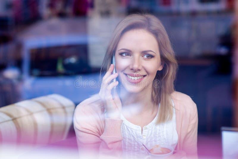 Donna in caffè bevente del caffè, facente una telefonata fotografia stock