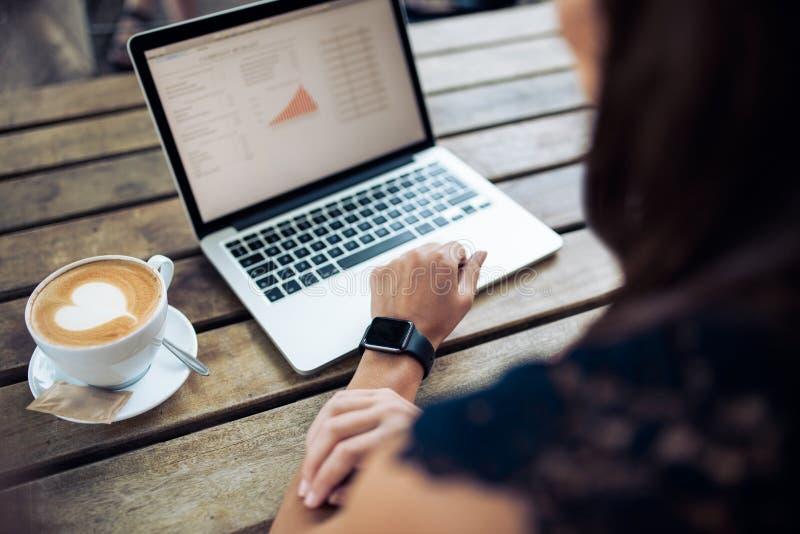 Donna in caffè facendo uso di ultimi dispositivi di tecnologia fotografie stock libere da diritti