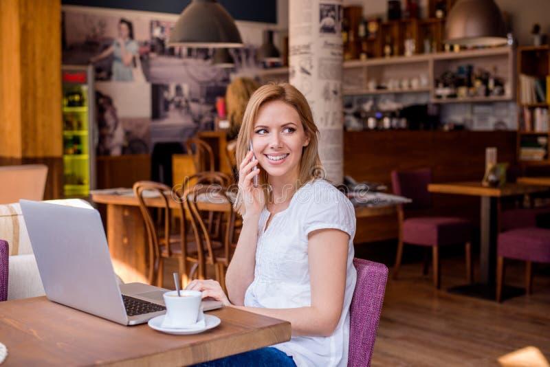 Donna in caffè, parlando sul telefono, lavorante al taccuino fotografia stock libera da diritti