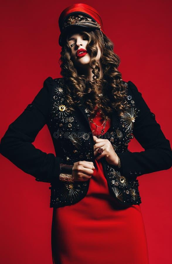 Donna calda in rivestimento nero con oro ed il vestito rosso fotografia stock libera da diritti