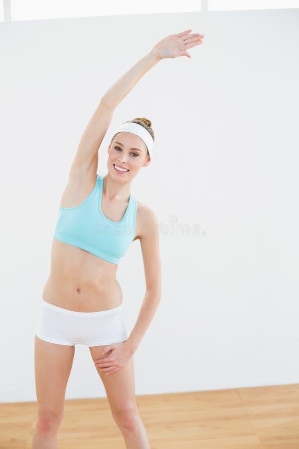 Donna calma adorabile che allunga il suo corpo che sorride alla macchina fotografica fotografia stock libera da diritti