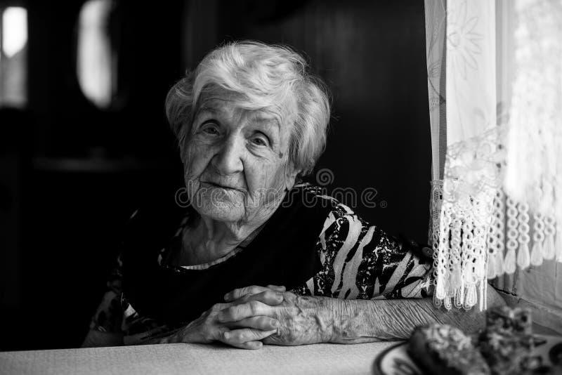 Donna calma anziana nella cucina della sua casa che si siede alla tavola fotografia stock