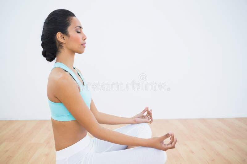Donna calma attraente che medita seduta nella posizione di loto immagine stock