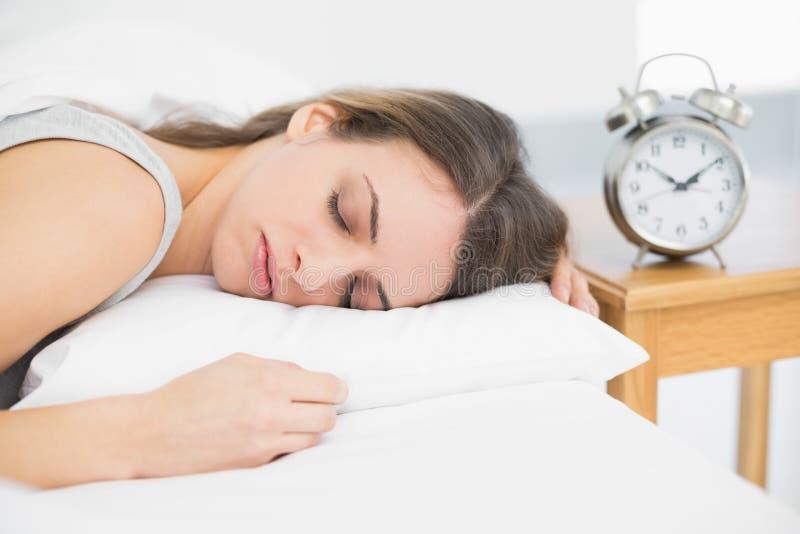 Donna calma attraente che si trova sul suo letto nell'ambito del sonno della copertura fotografie stock