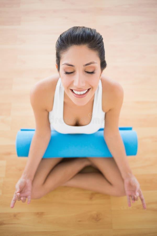 Donna calma con la sua stuoia di esercizio che si siede nella posa del loto fotografie stock
