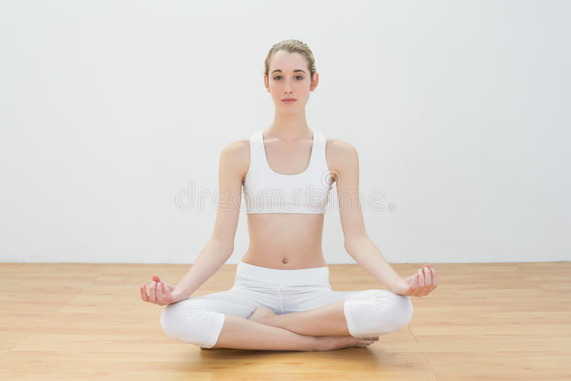 Donna calma messa a fuoco che medita seduta nella palestra immagini stock